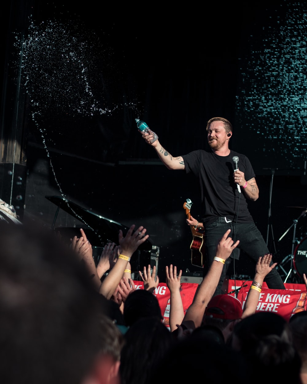 man in black crew neck t-shirt standing on stage