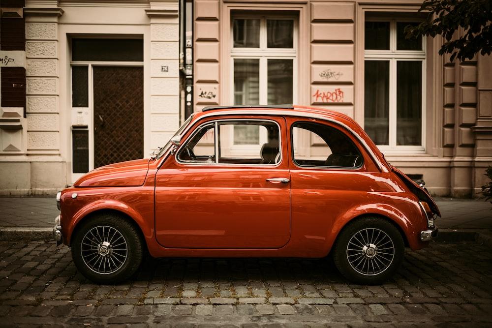 red volkswagen beetle parked on sidewalk during daytime