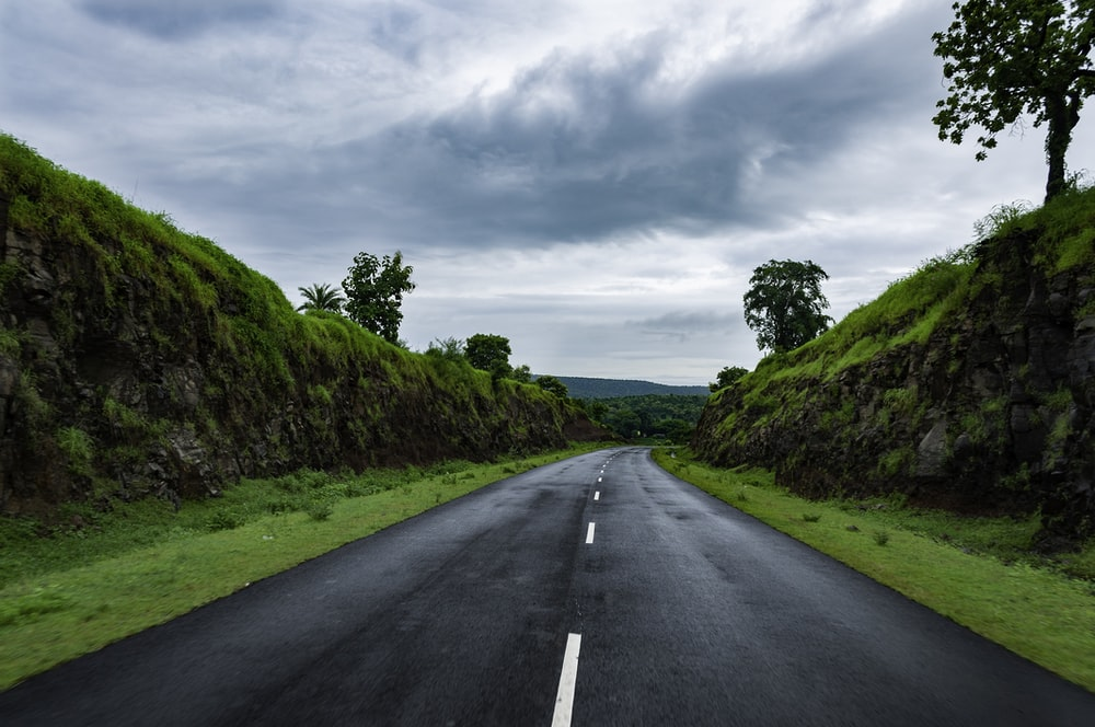 gray concrete road between green grass field under white clouds during daytime