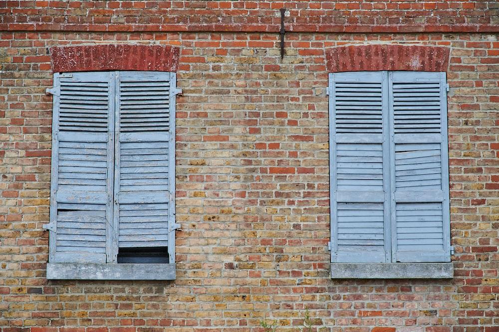 blue wooden window on brown brick wall