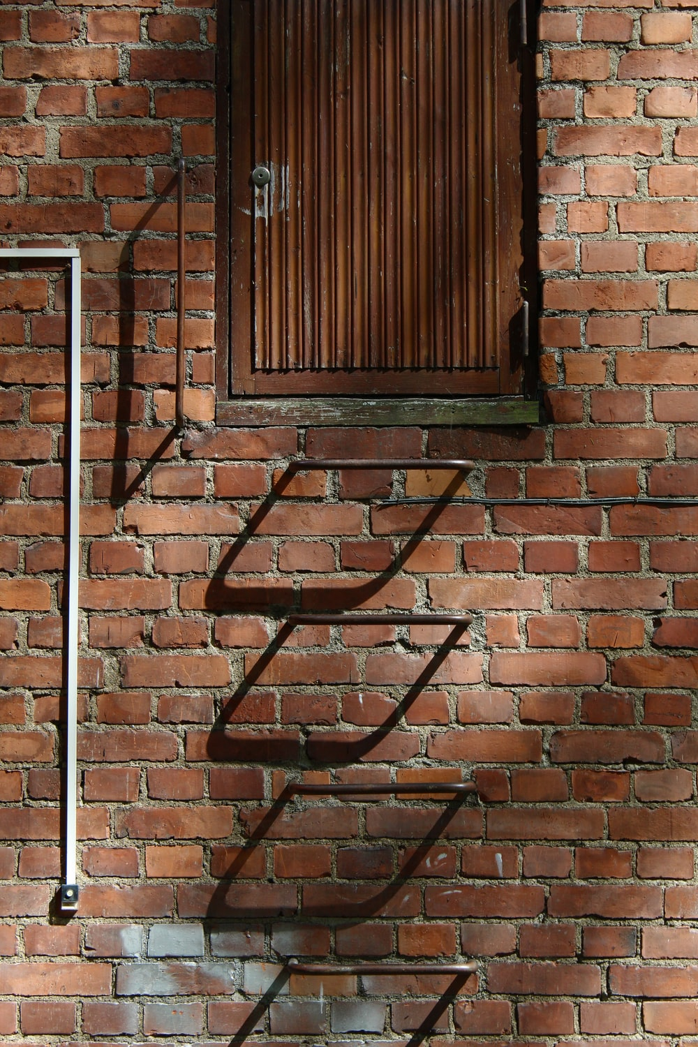black metal window frame on brown brick wall