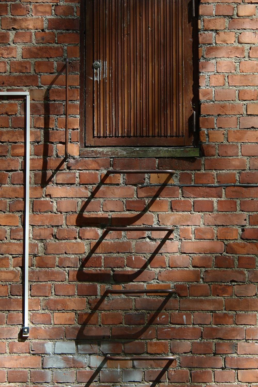 black metal window frame on brown brick wall