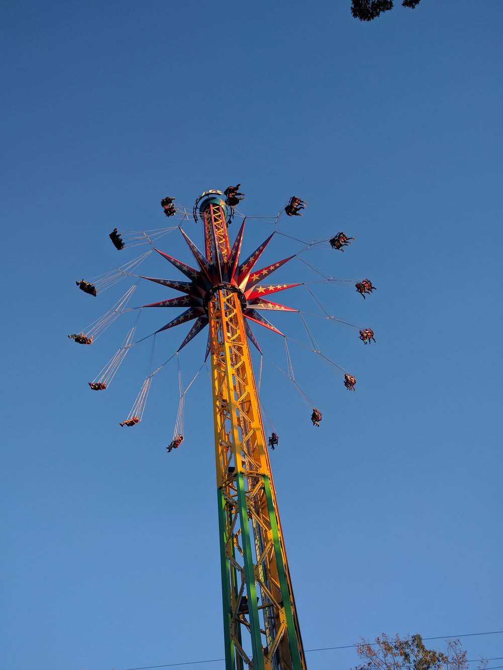 people riding on green and red roller coaster during daytime