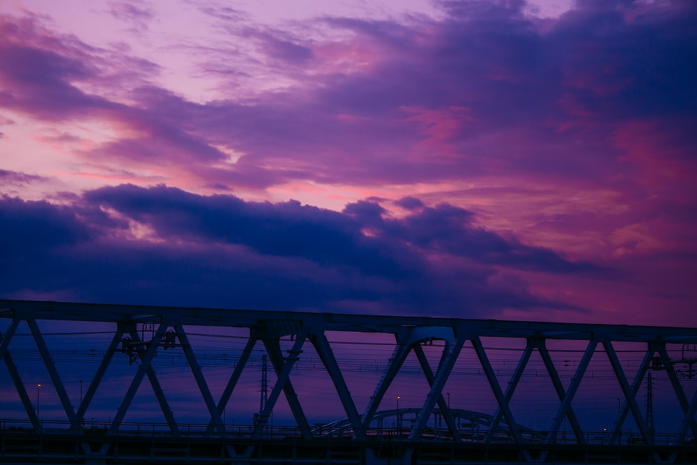 silhouette of bridge under cloudy sky during sunset