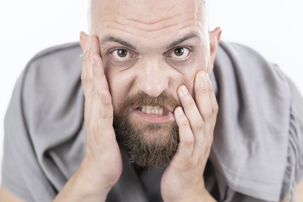 man in gray dress shirt covering his face