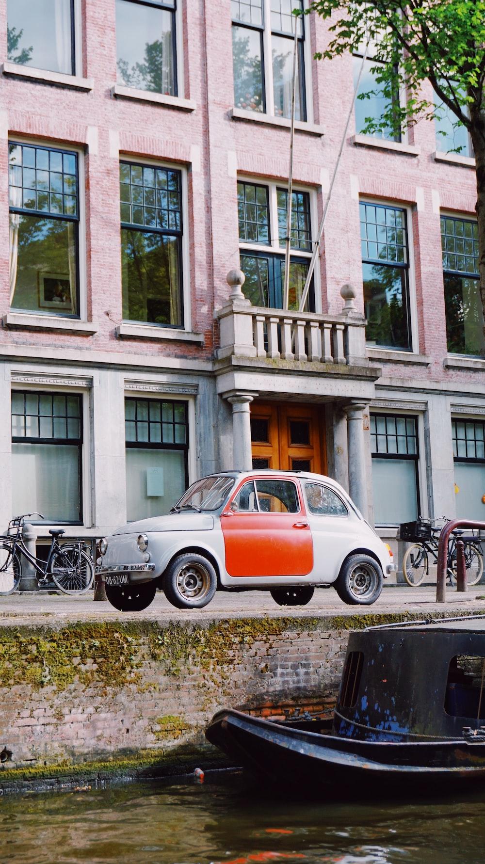 orange and white car parked beside black motorcycle during daytime