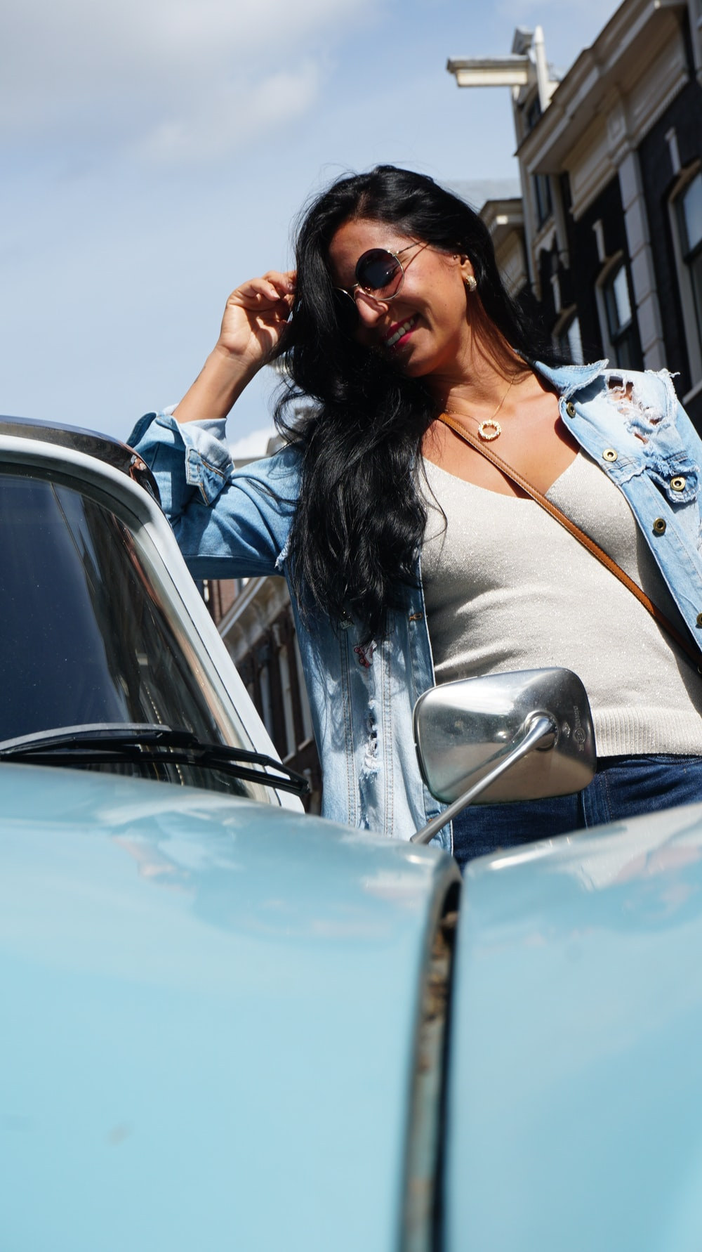 woman in white long sleeve shirt sitting on car