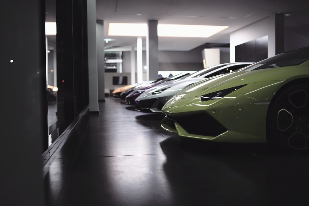 green and black sports car parked in building