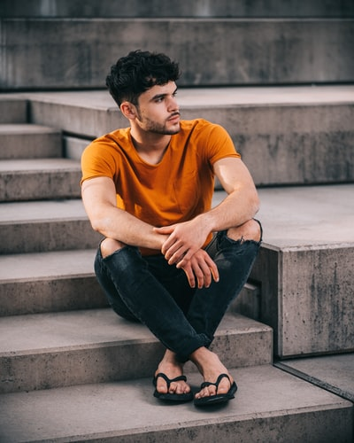 man in yellow crew neck t-shirt and black denim jeans sitting on concrete stairs