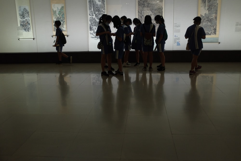 group of people standing on white floor tiles