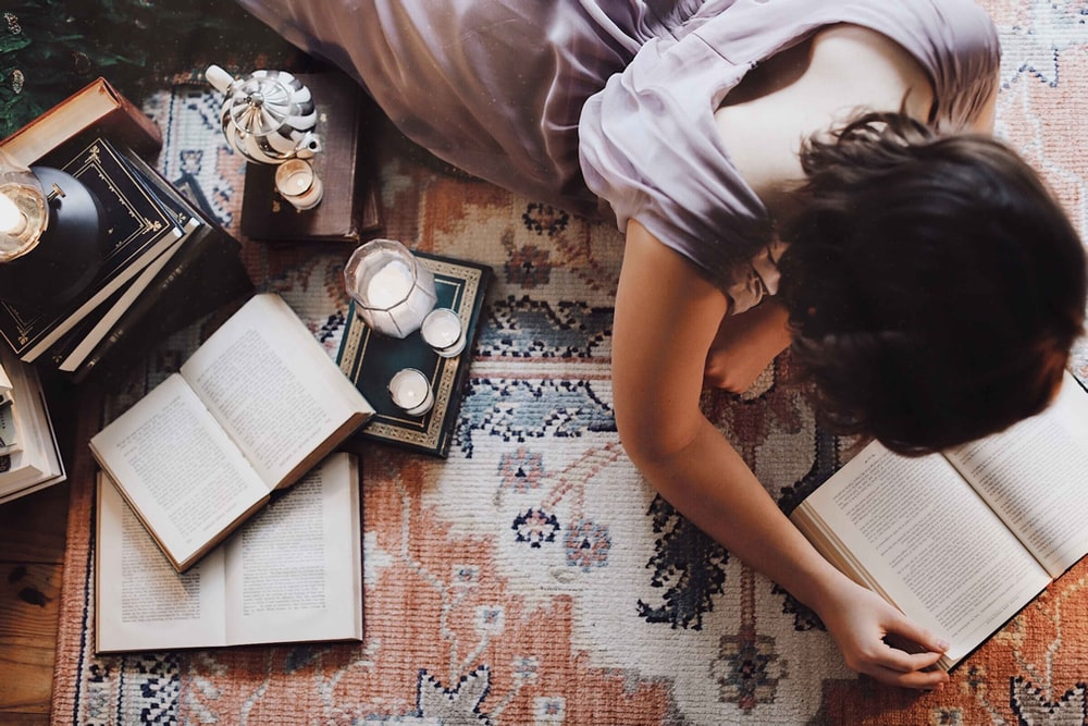 woman in white t-shirt lying on floor with books and photos