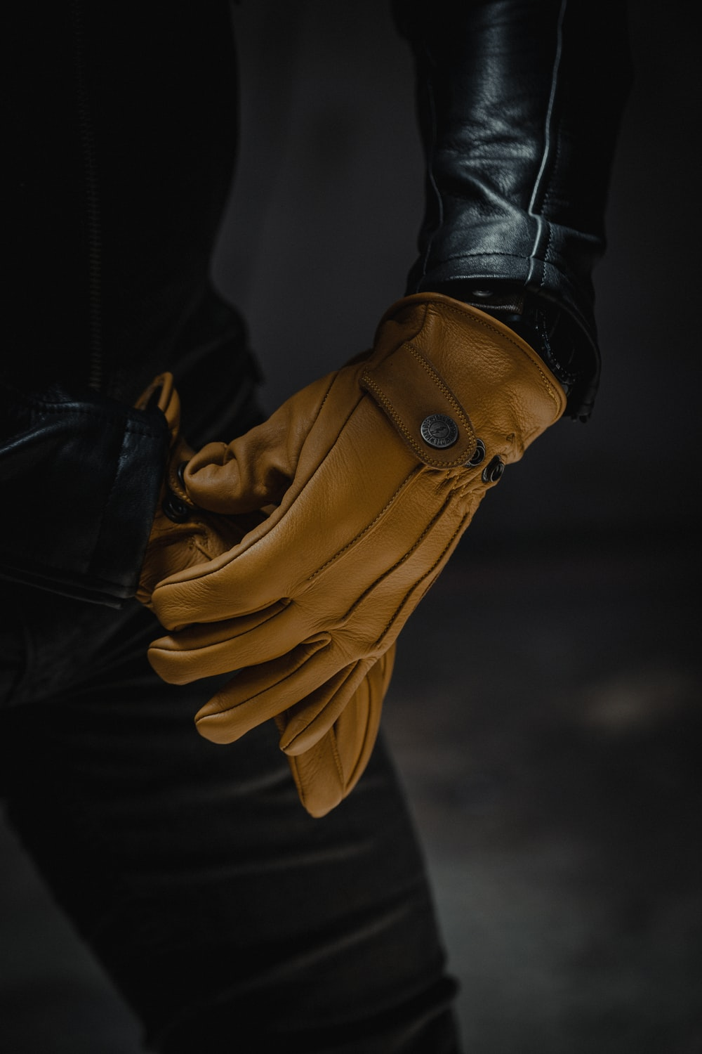 person wearing black leather gloves