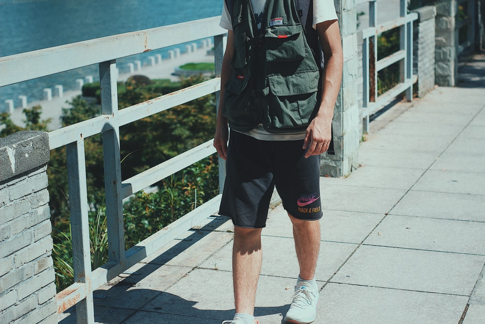 man in black shorts and white sneakers standing on gray concrete floor