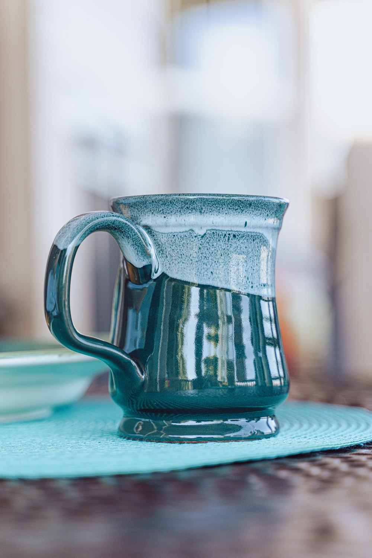 blue ceramic mug on blue table cloth