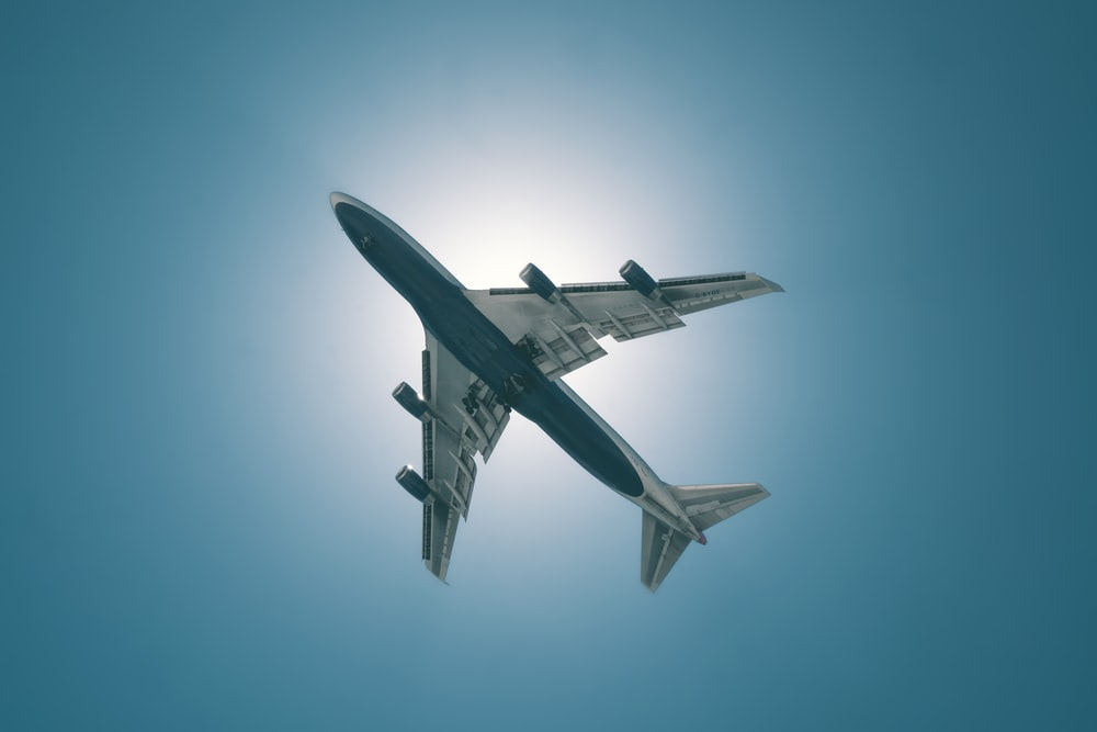 white and black airplane in mid air during daytime