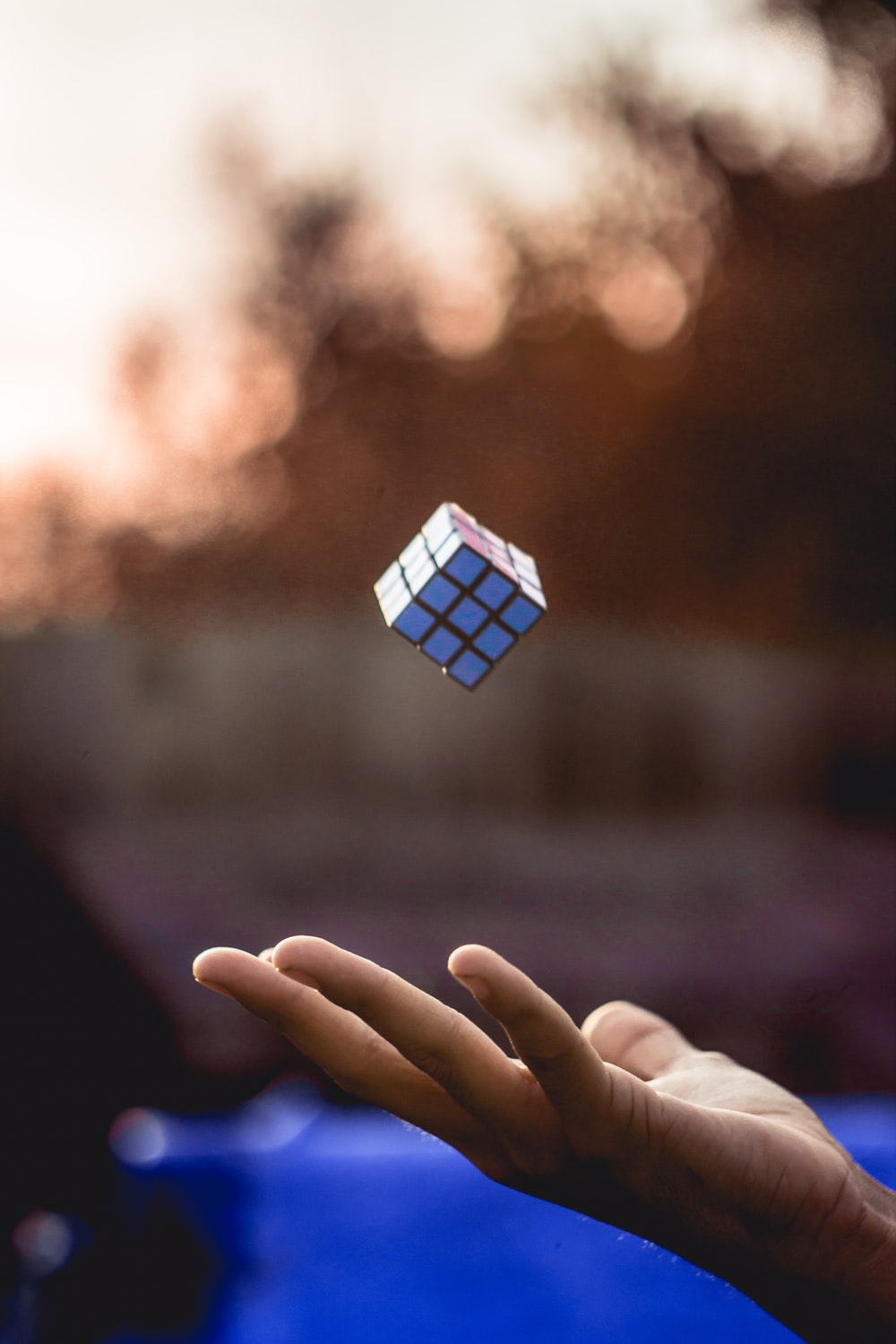 person holding blue and white cube