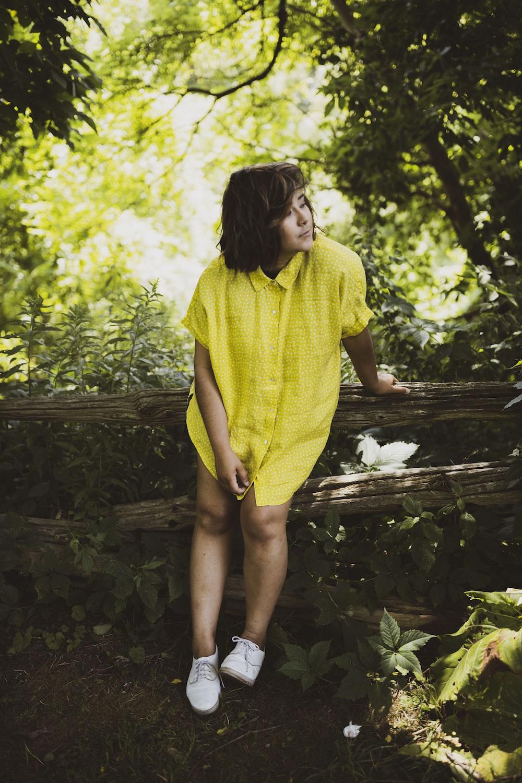 woman in yellow dress standing on brown wooden bridge