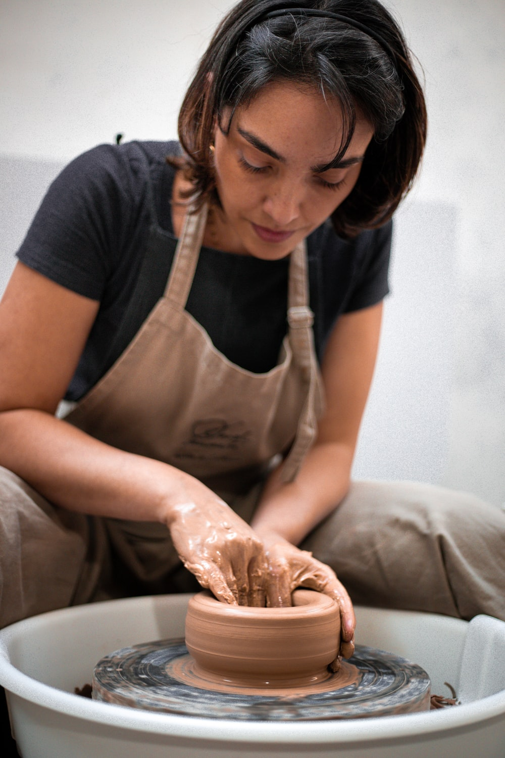 woman in gray apron holding brown clay pot