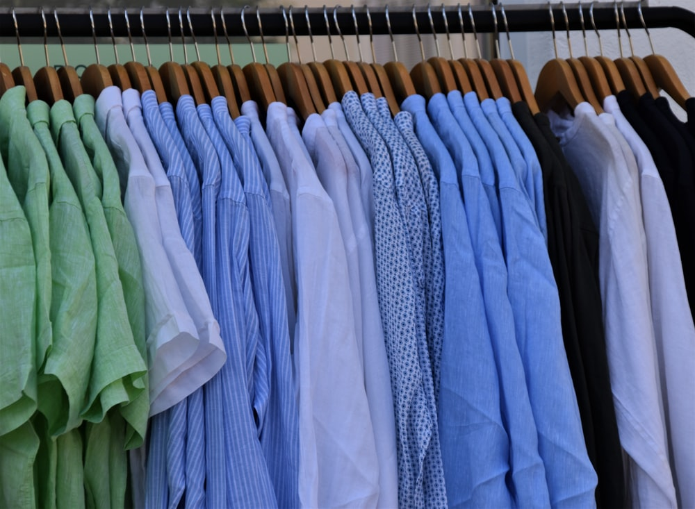 white blue and gray clothes hanging on brown wooden rack