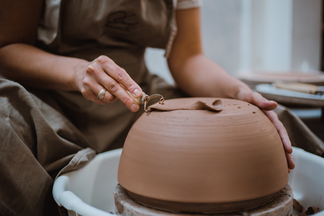 Person In Brown Shirt Holding Brown Clay Pot - unsplash