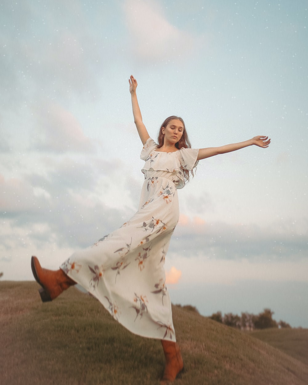 woman in white dress raising her right hand
