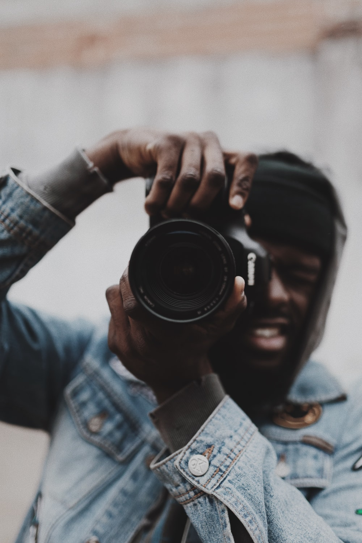 man in blue denim jacket holding black camera