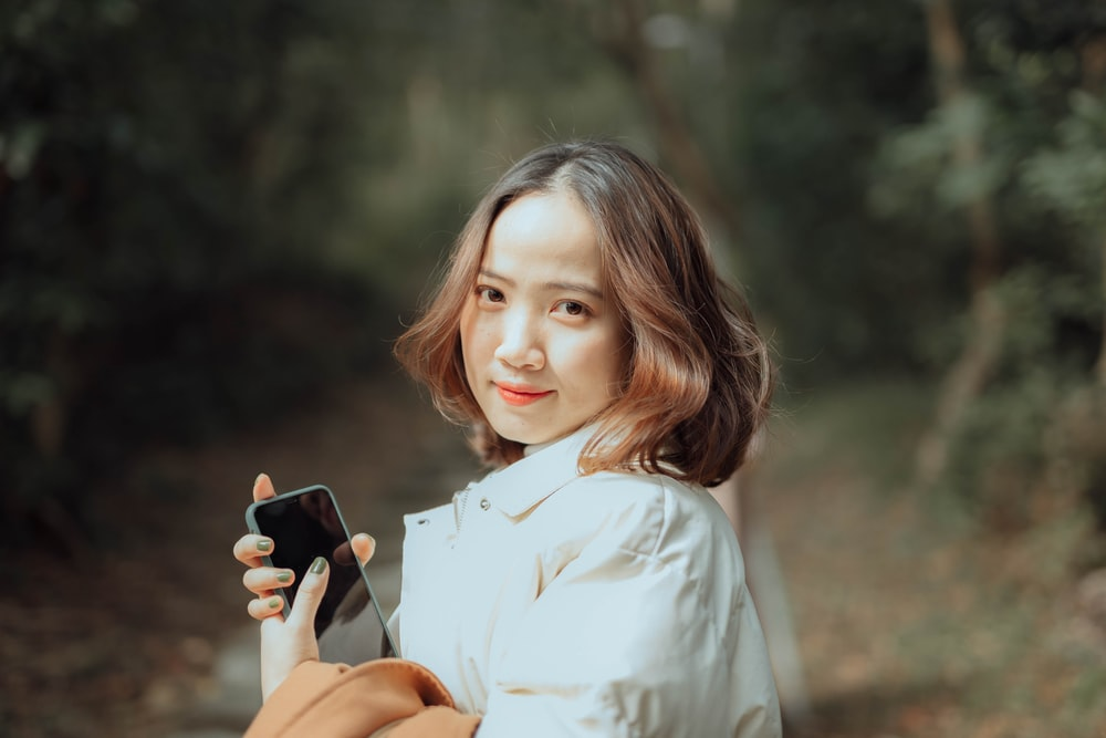 woman in white button up shirt holding black smartphone