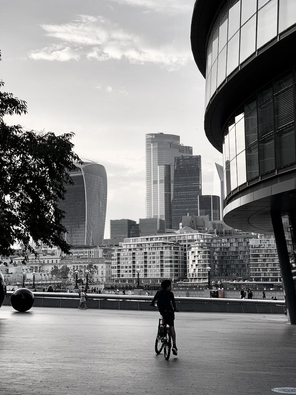 man in black jacket walking on sidewalk near city buildings during daytime