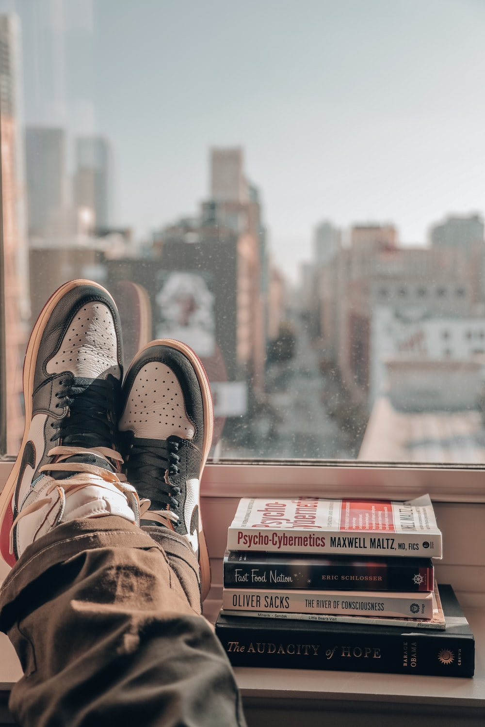 person in brown hiking shoes sitting on top of building during daytime