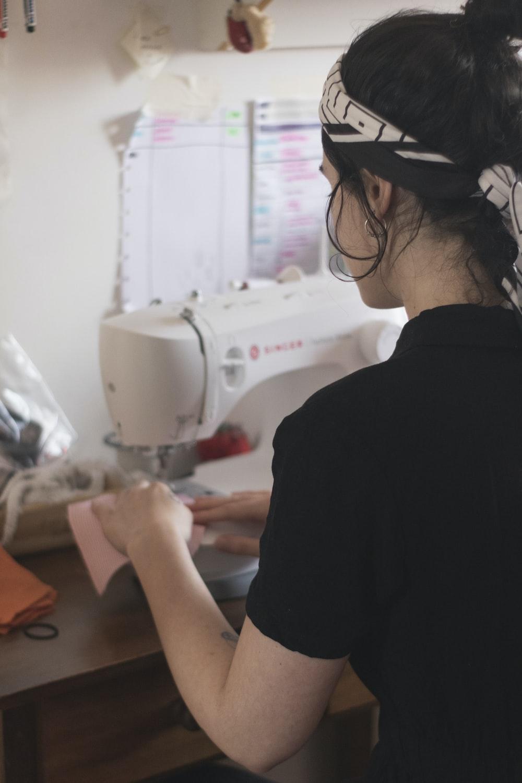 man in black shirt using sewing machine
