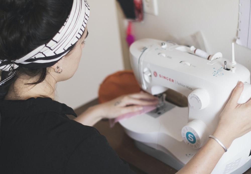 woman in black long sleeve shirt sewing