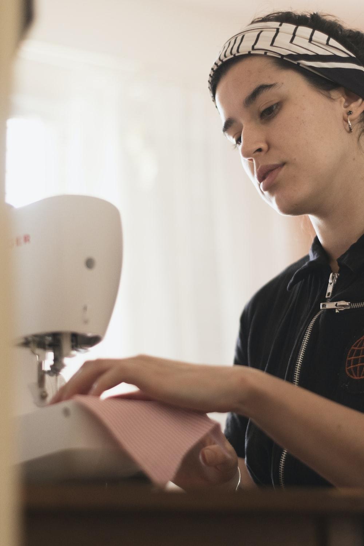 man in black polo shirt using white sewing machine