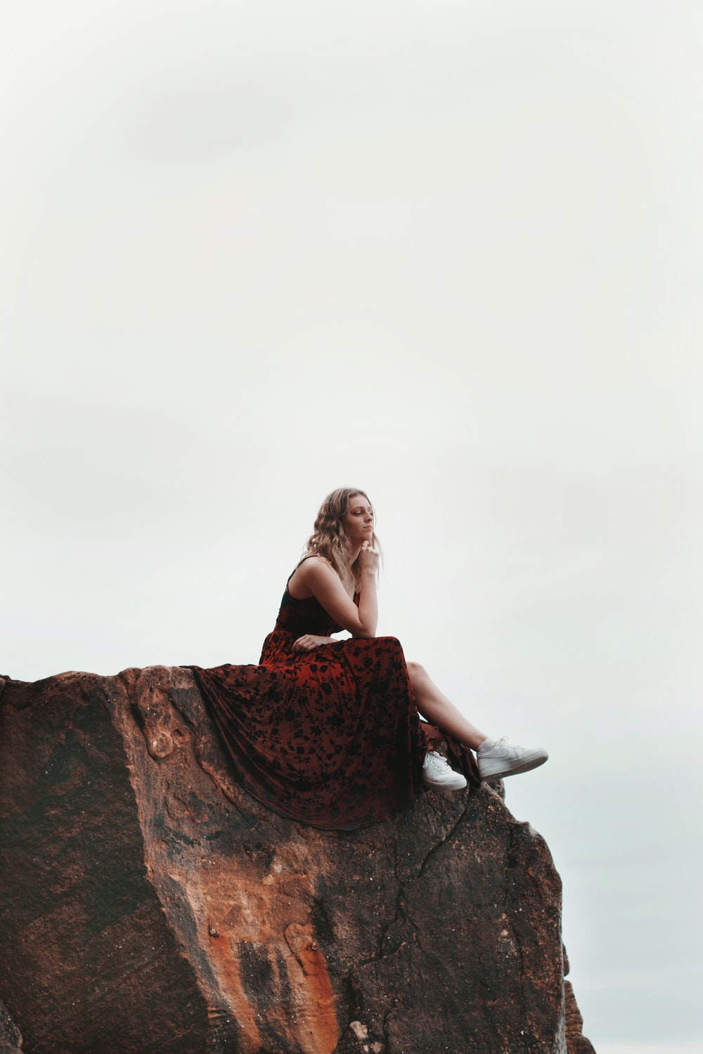 woman in black and red floral dress sitting on rock