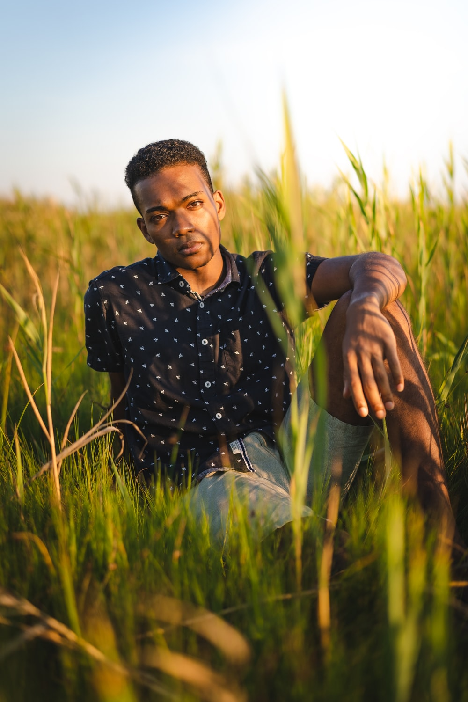 man in black and white polka dot dress shirt sitting on green grass field