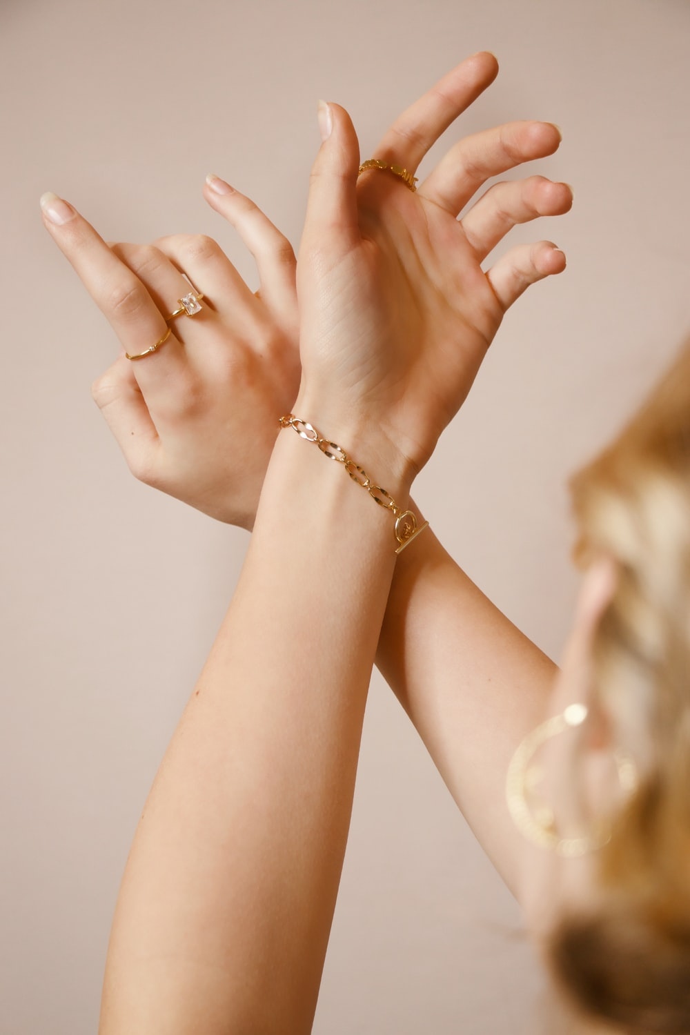 woman wearing gold ring and gold bracelet
