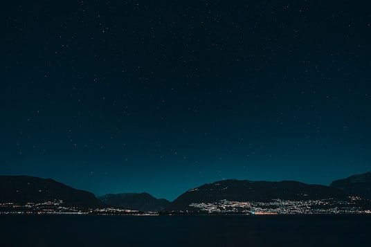 silhouette of mountain near body of water during night time