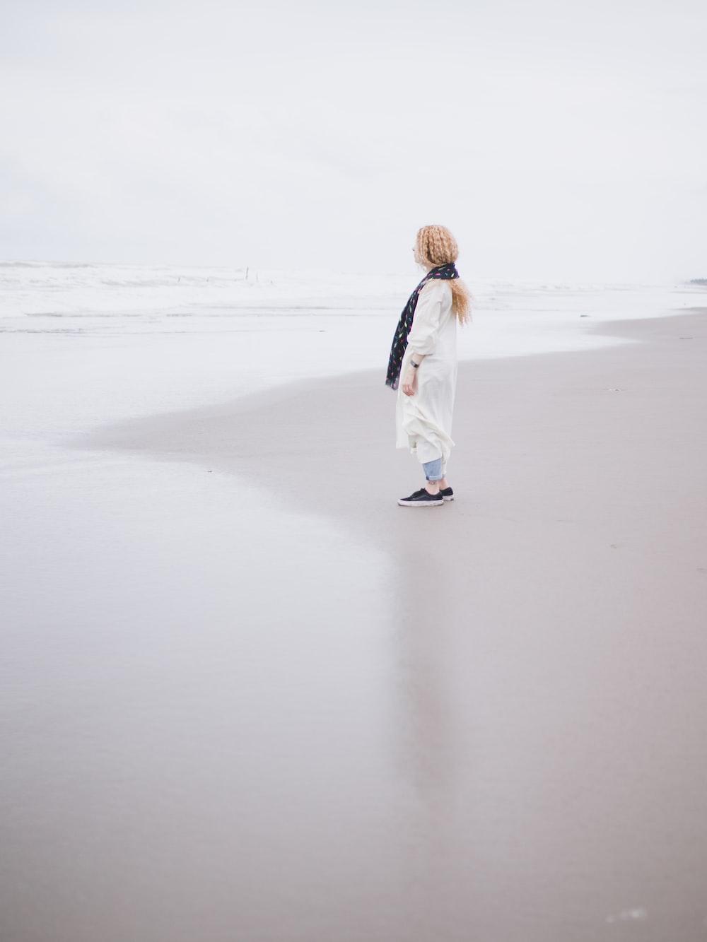 woman in white coat walking on white sand during daytime