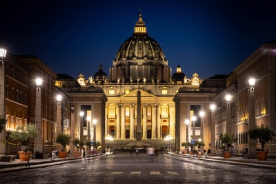 people walking near brown concrete building during nighttime vatican city teams background