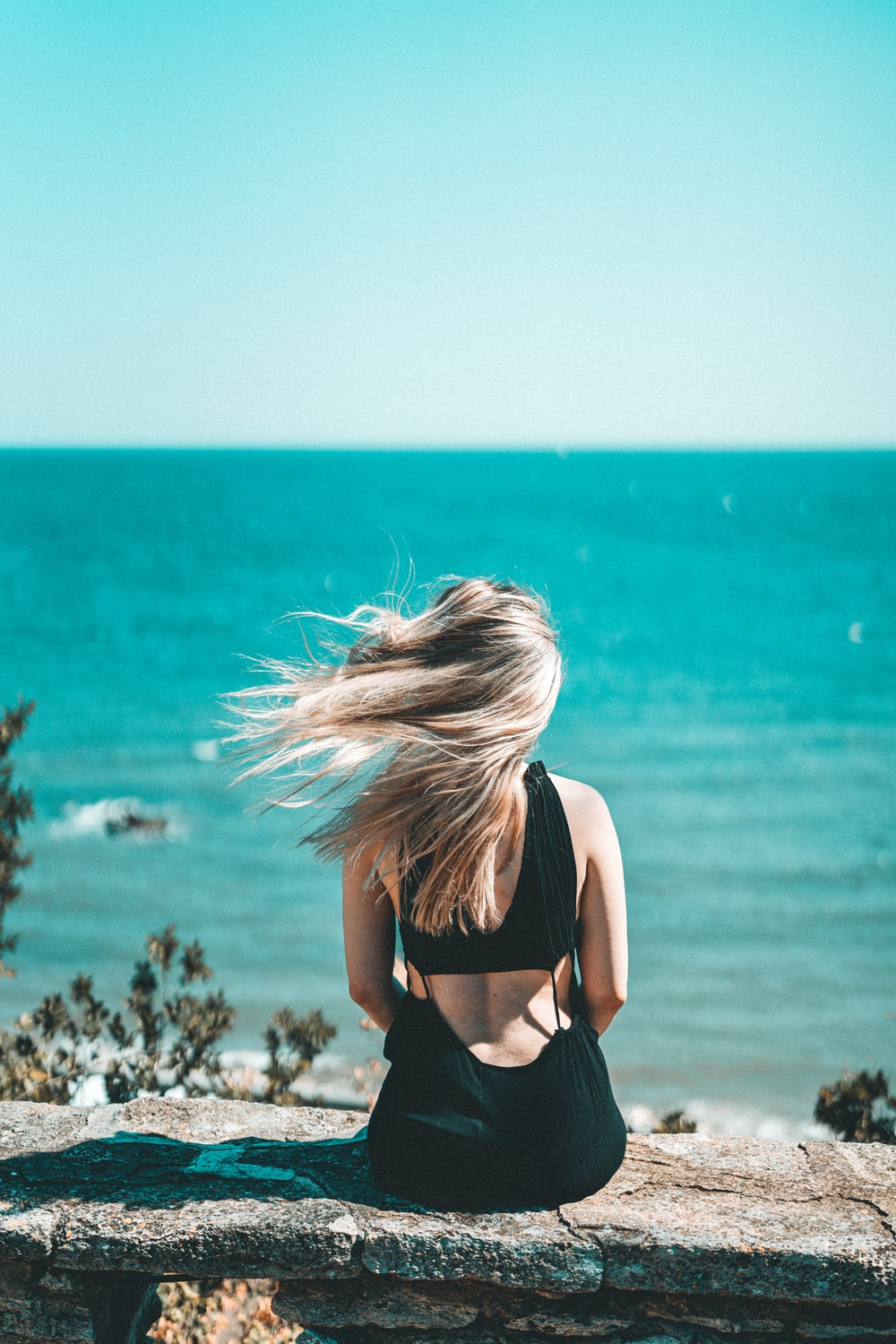 woman in black brassiere standing near sea during daytime