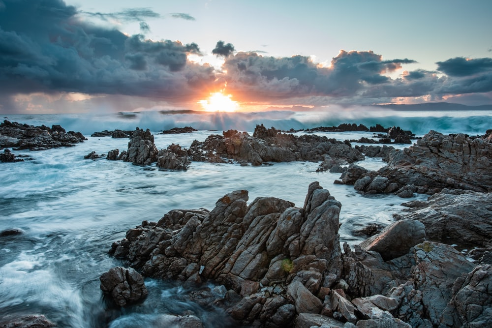 rocky shore under cloudy sky during daytime