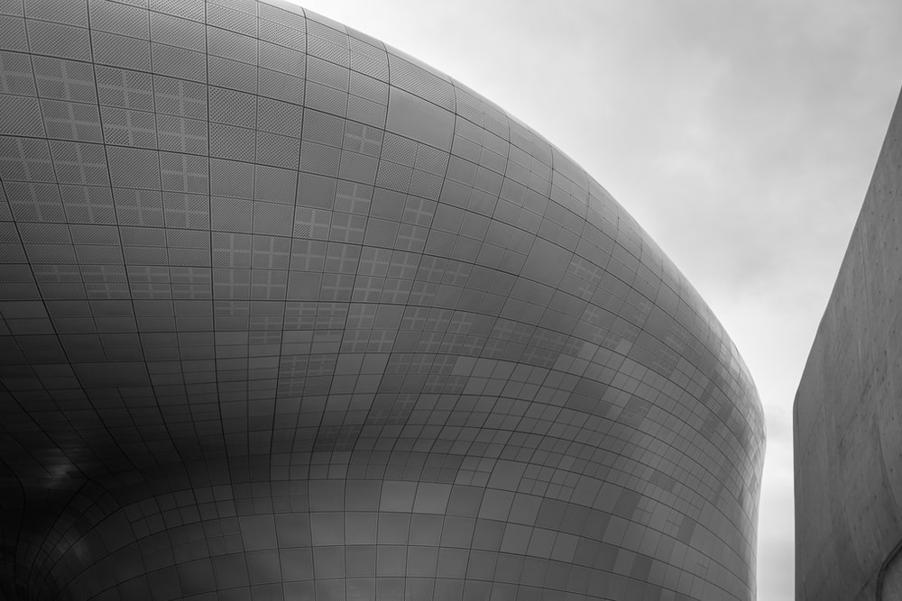 grayscale photo of round concrete building