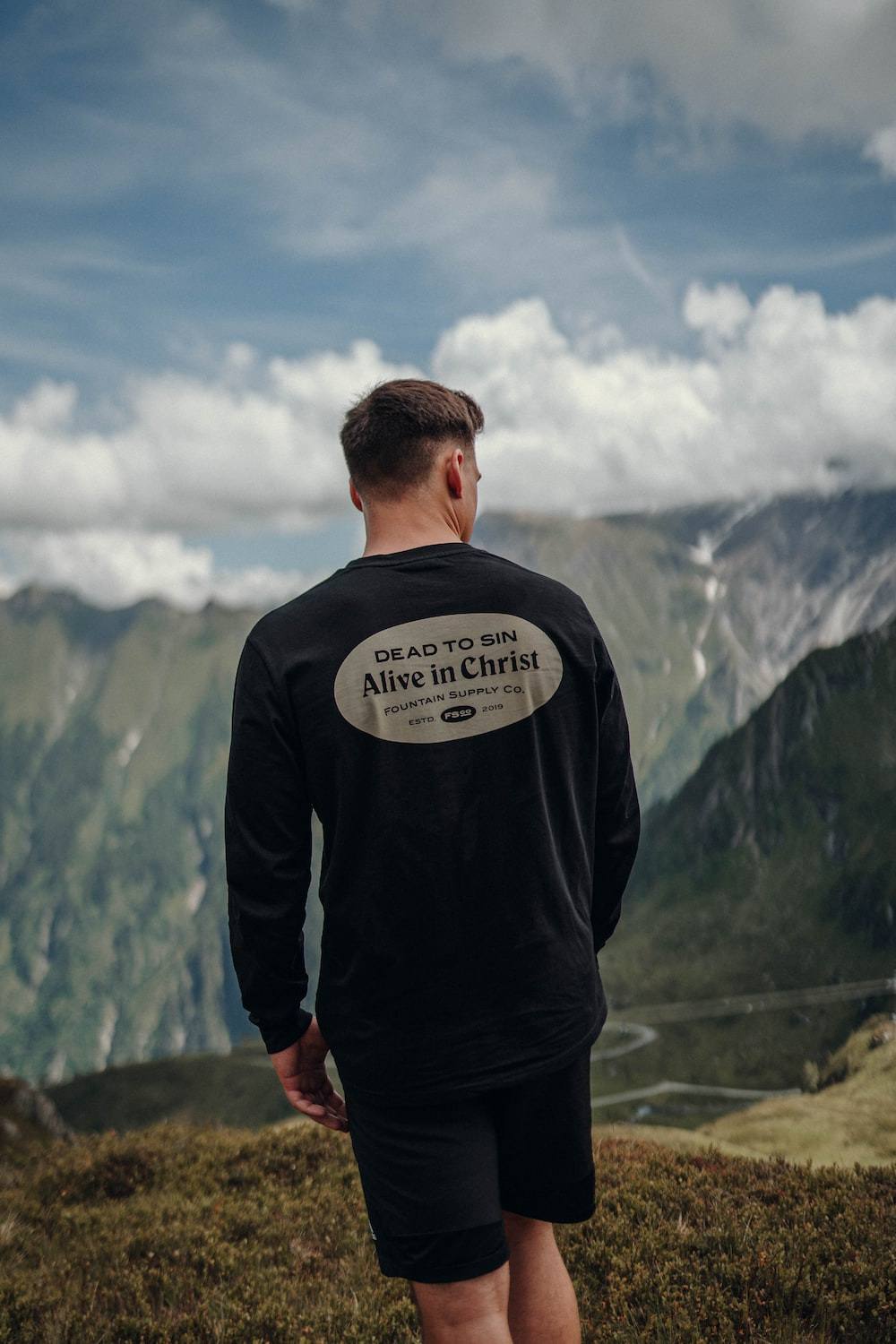 man in black and white long sleeve shirt standing on mountain under blue and white cloudy