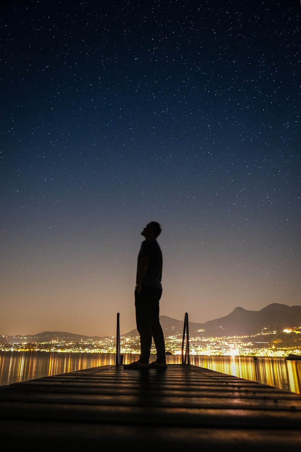 silhouette of man standing on dock during night time