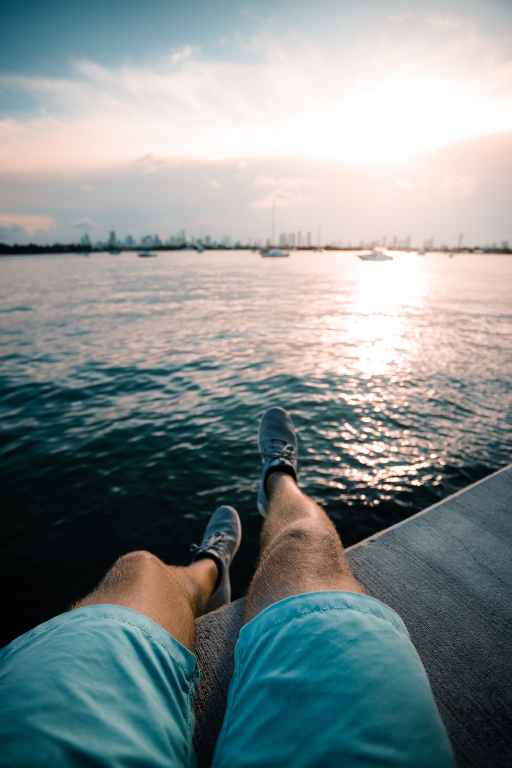 person in blue denim shorts and black shoes sitting on dock over the sea during daytime