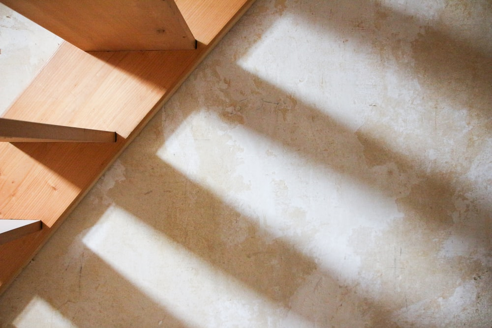 brown wooden staircase with white concrete wall
