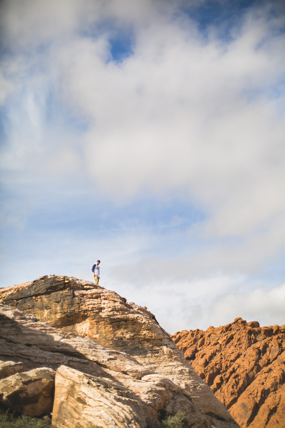 person standing on brown rock formation under white clouds and blue sky during daytime