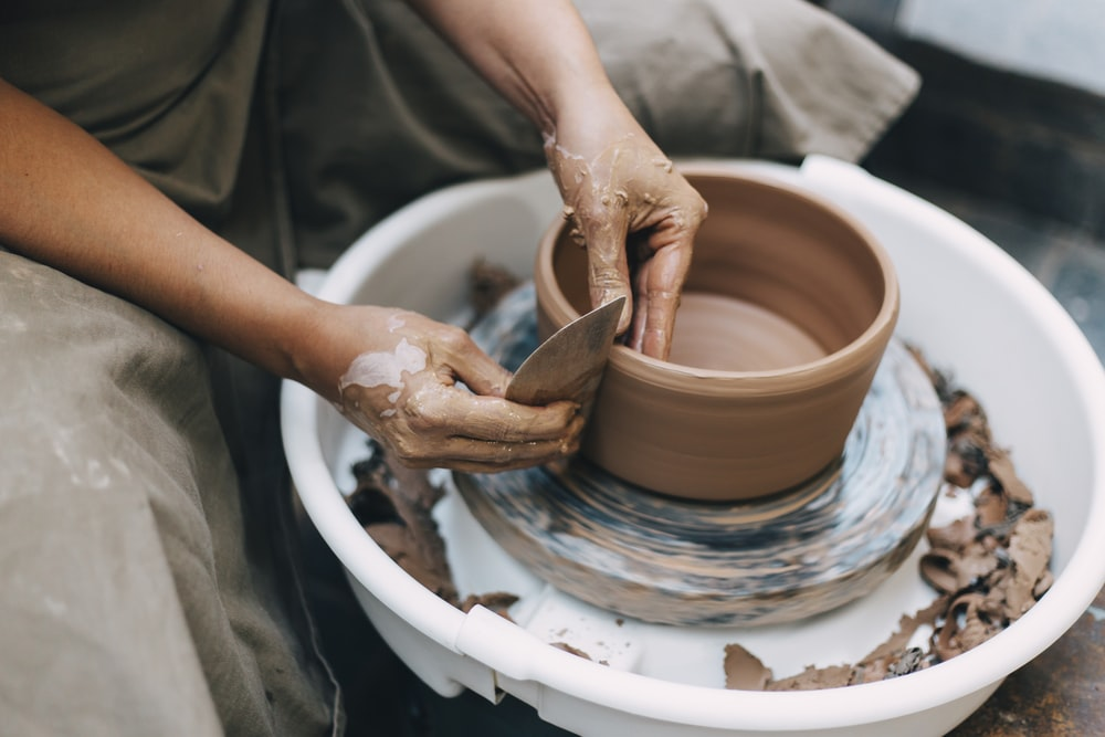 person making clay pot on white round plate