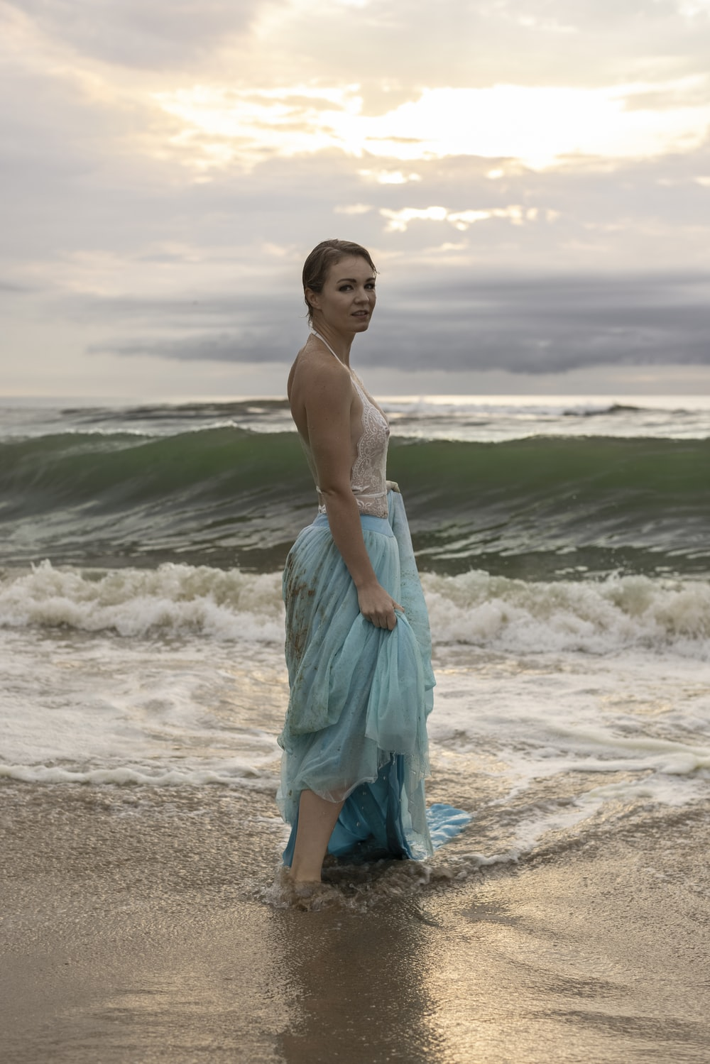 woman in blue dress standing on beach during daytime