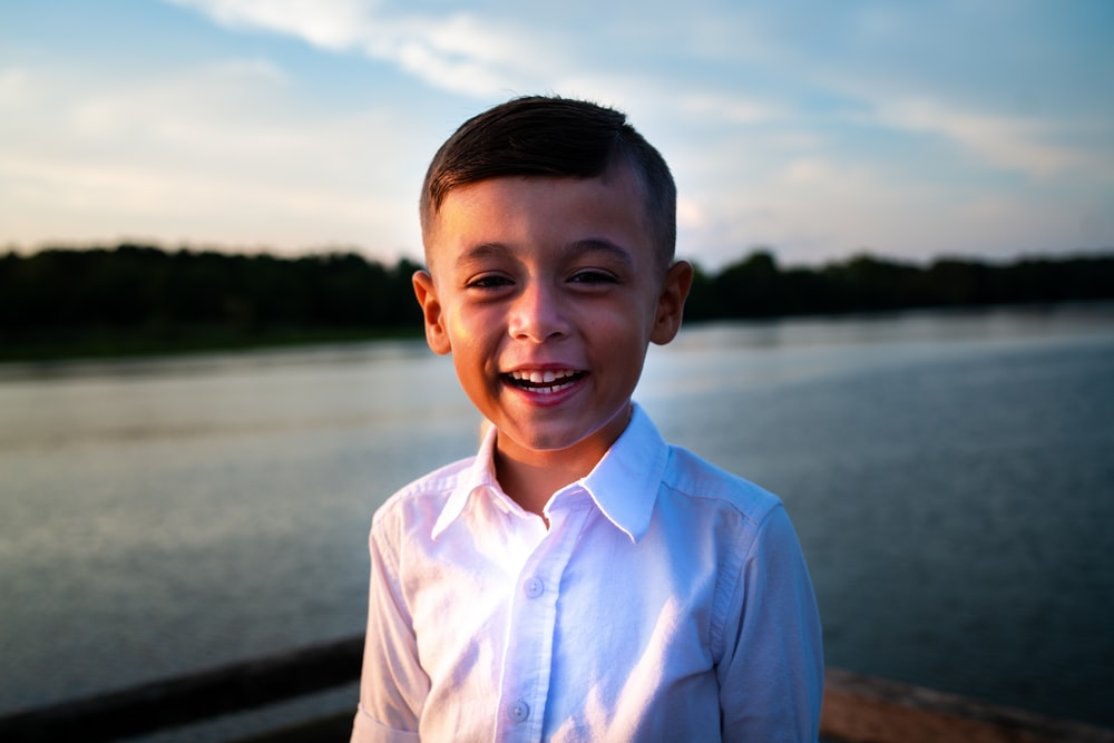 smiling boy in white dress shirt standing near body of water during daytime