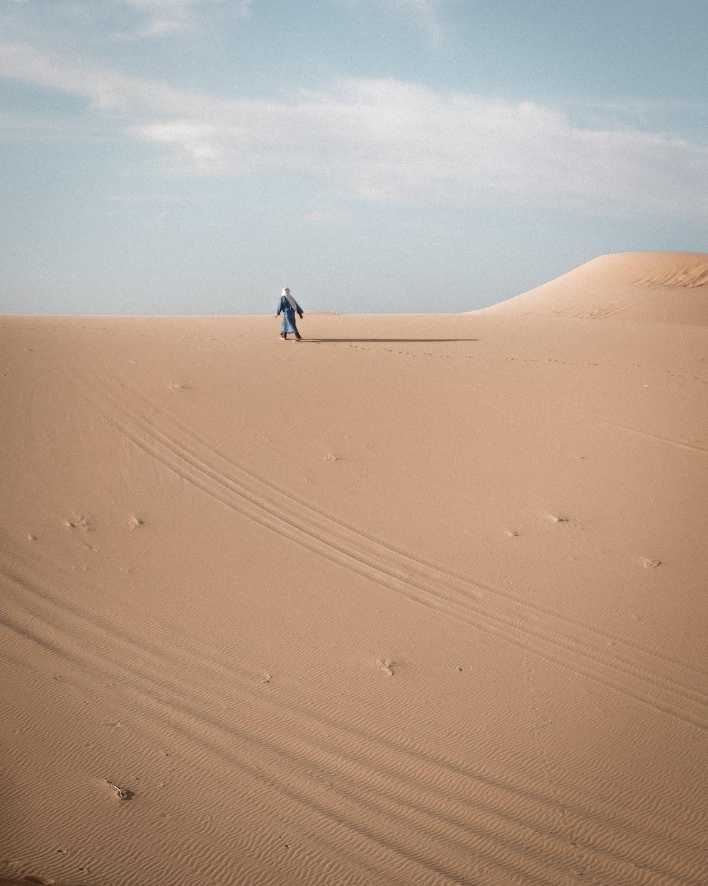 person in black jacket walking on desert during daytime